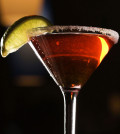 Close-up of red martini with lime.