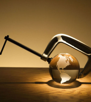Glass globe being held by C clamp on brown wooden background.