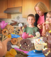 Two children are eating messy junk food snacks such as cookies, donuts and cupcakes in the kitchen with an angry mother.