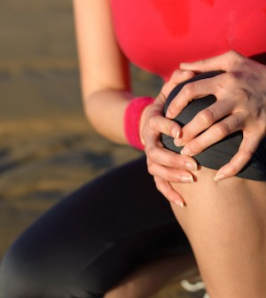Runner sport knee injury. Woman in pain while running in beach. Caucasian female athlete with painful kneecap.