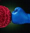 Cancer fight medical concept with an arm of a doctor wearing a blue boxing glove fighting a group of malignant human cells as a health care metaphor for researching a cure for dangerous tumors and therapy to remove illness.