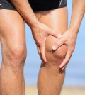 Runner injury - Man running with knee pain. Close-up view of runner injured jogging on the beach clutching his knee in pain. Male fitness athlete.