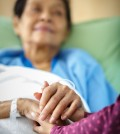 Caring hands holding kind elderly lady's hands in bed at hospital