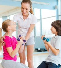 Supporting kids in training. Cheerful instructor helping children with exercising in health club
