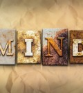 "The word ""MIND"" written in rusty metal letterpress type on a crumbled aged paper background."