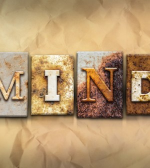 """The word """"MIND"""" written in rusty metal letterpress type on a crumbled aged paper background."""