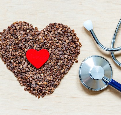Dieting healthy living concept. Buckwheat groats heart shaped and stethoscope on wooden surface.. Healthy food good for cardiovascular system